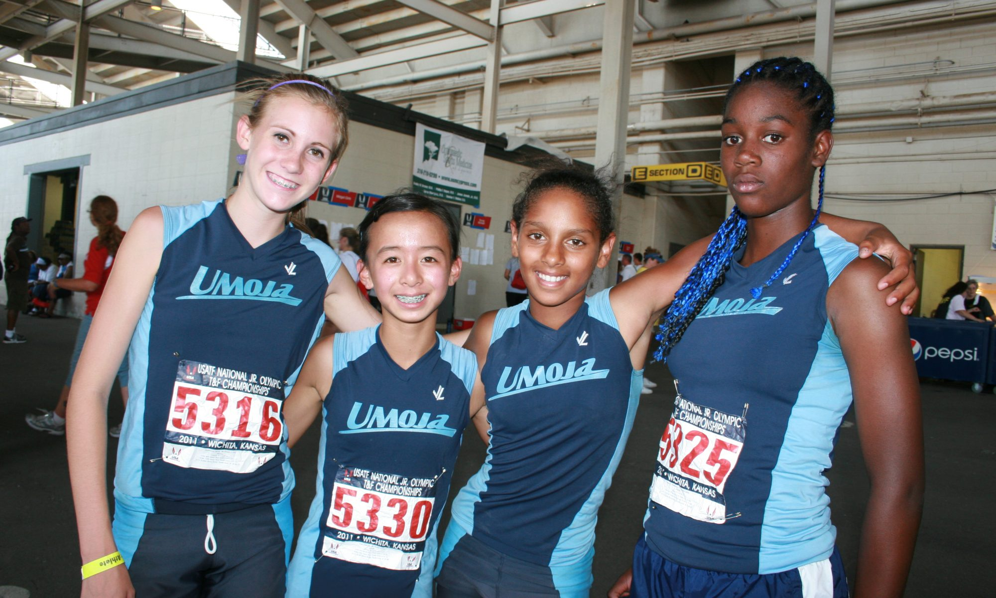 4 girls in track uniforms smiling and facing the camera with arms around each other.