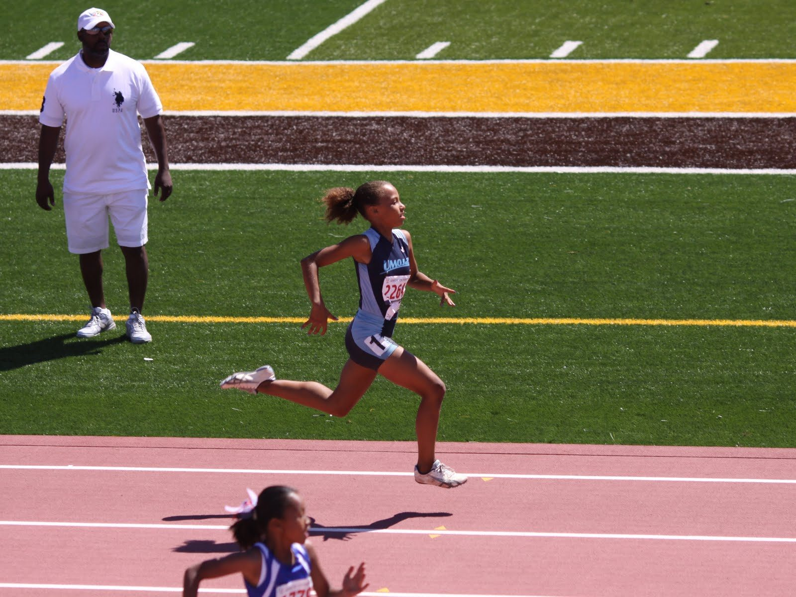 A girl is running on a track.